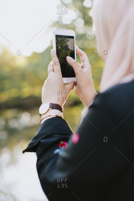 Young woman taking photograph with smartphone