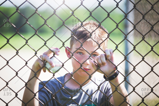 View through chicken wire fence of boy looking at camera
