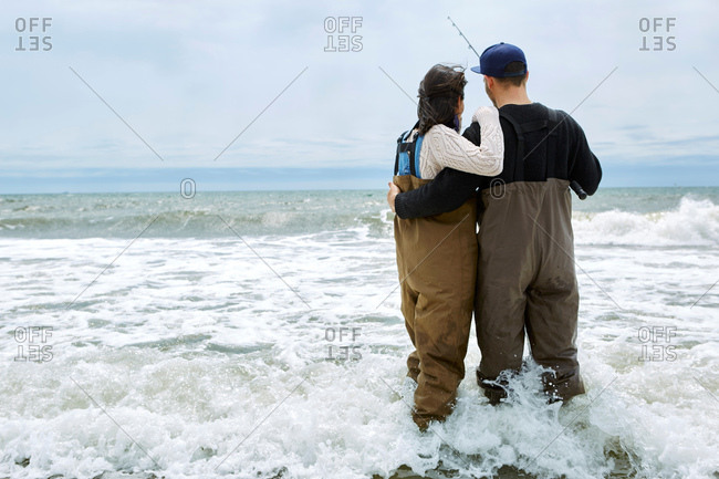 Rear view of young couple in waders sea fishing