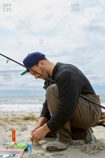 Crouching young man preparing fishing hook on beach