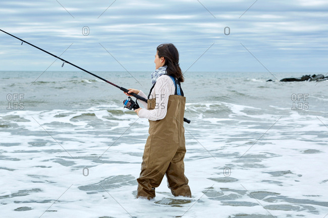 Young woman in waders sea fishing knee deep in water