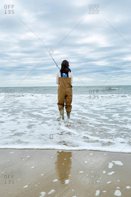 Rear view of young woman in waders sea fishing