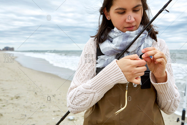 Young woman in waders preparing fishing rod line on beach