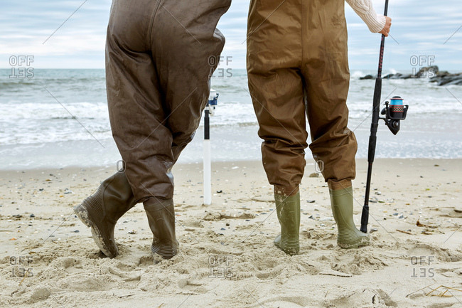 Waist down rear view of young couple in sea fishing waders on beach