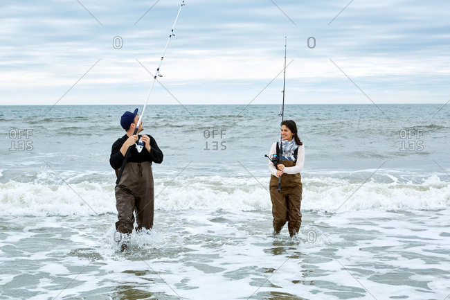 Young couple in waders sea fishing knee deep in water