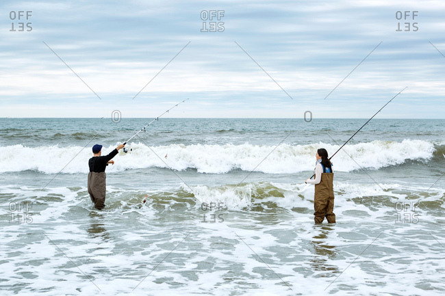 Young couple in waders, casting off sea fishing rods in sea