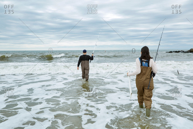 Young sea fishing couple in waders, wading in sea