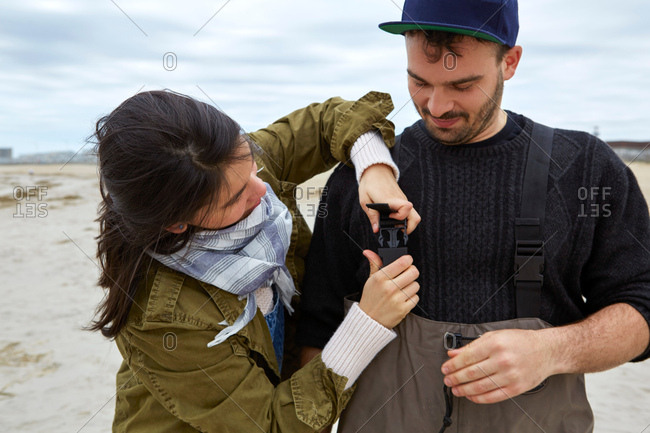 Young sea fishing couple fastening waders on beach