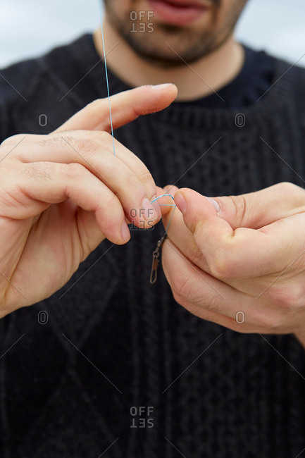 Close up of sea fishing man\'s hands preparing fishing line