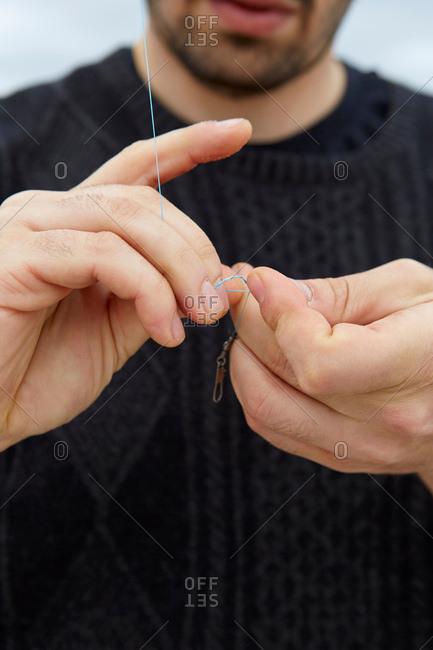 Close up of sea fishing man\'s hands preparing fishing line