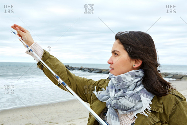 Young woman adjusting fishing rod line on beach