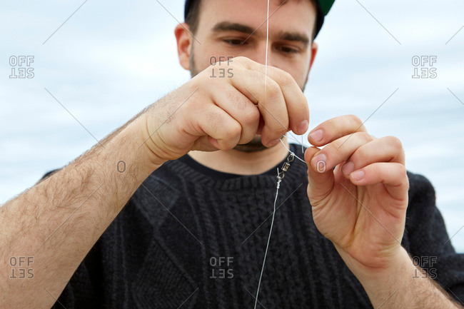 Young man attaching fishing hook to fishing line