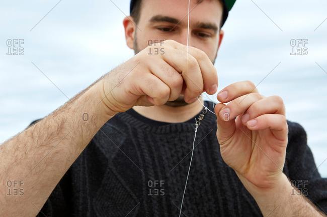 Young man attaching fishing hook to fishing line