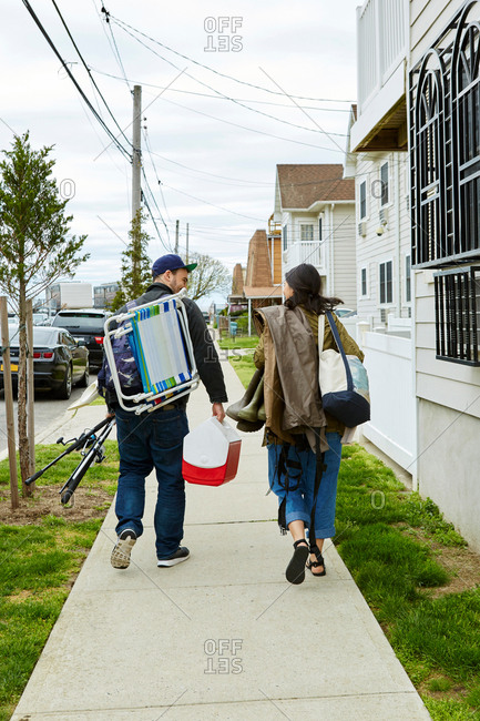 Rear view of young couple carrying fishing equipment on sidewalk