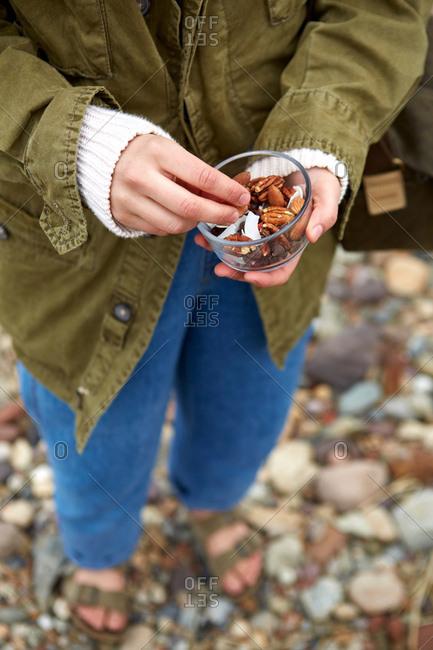 Waist down shot of woman on shingle beach holding fresh nuts