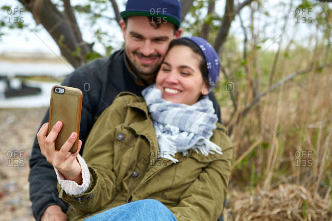 Happy young couple taking smartphone selfie on beach