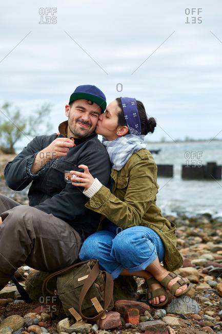 Young woman kissing boyfriend on cheek on beach