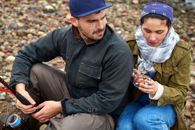 Young  sea fishing couple sitting on shingle  beach