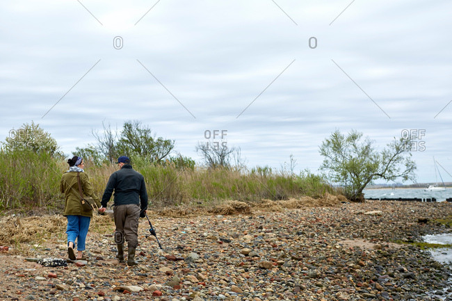 Rear view of young sea fishing couple strolling on shingle  beach
