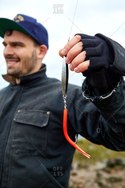 Young man holding fishing line and hook