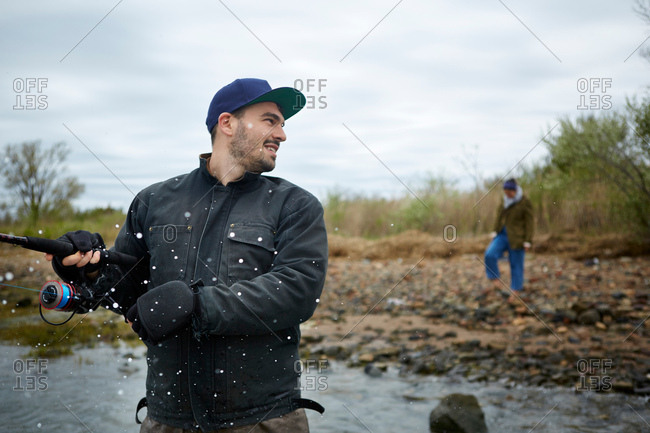 Young man getting splashed by sea while sea fishing