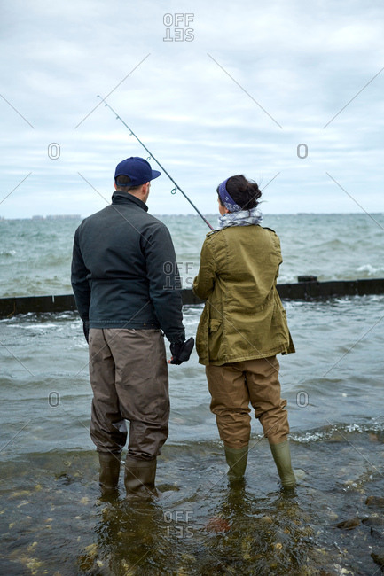 Rear view of young man ankle deep in water teaching girlfriend sea fishing
