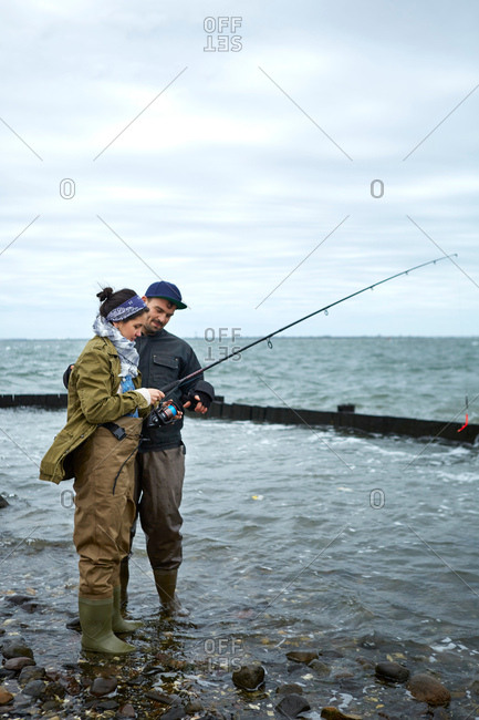 Young man ankle deep in water teaching girlfriend sea fishing
