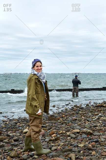 Portrait of young woman on beach while boyfriend sea fishing