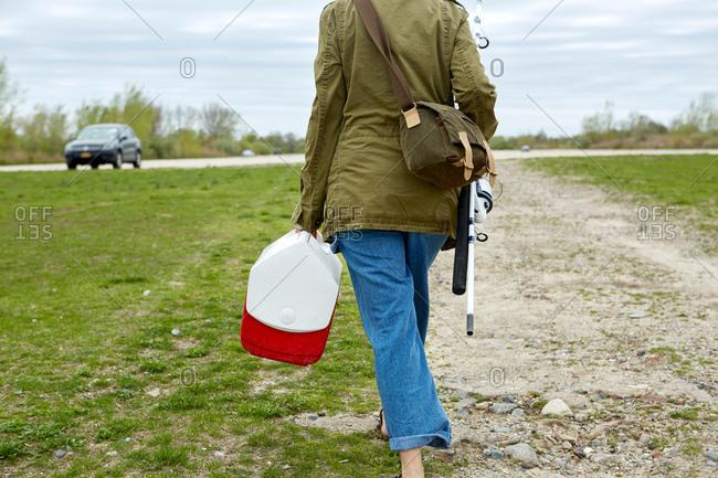 Young woman walking toward car, carrying fishing rod and tackle box, rear view