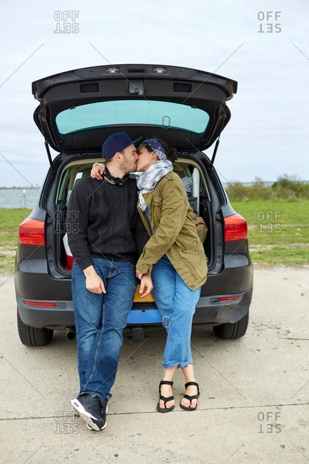 Young couple sitting in open car boot, kissing