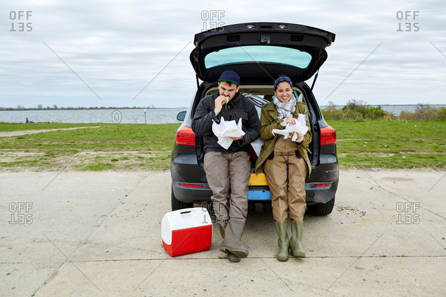 Young couple sitting in open car boot, eating food from paper