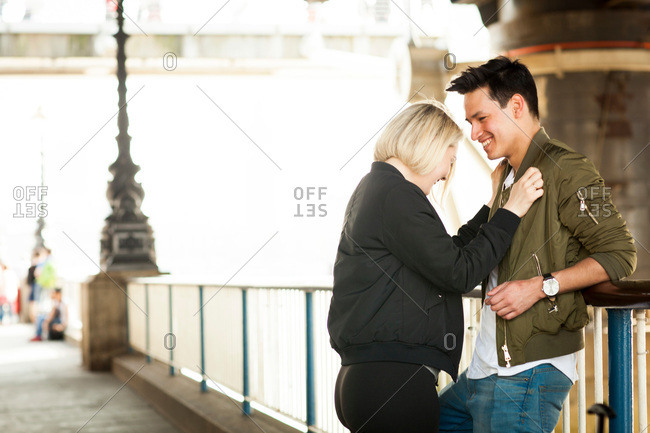 Young couple, standing underneath bridge, face to face, laughing