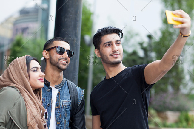 Three friends in street, taking selfie with smartphone