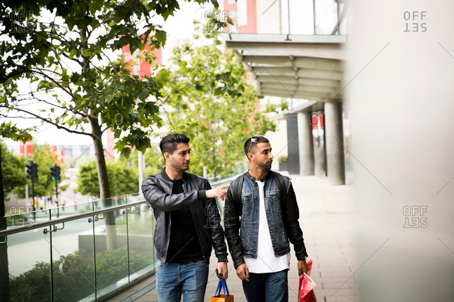 Two young men, walking past shops, pointing in shop window