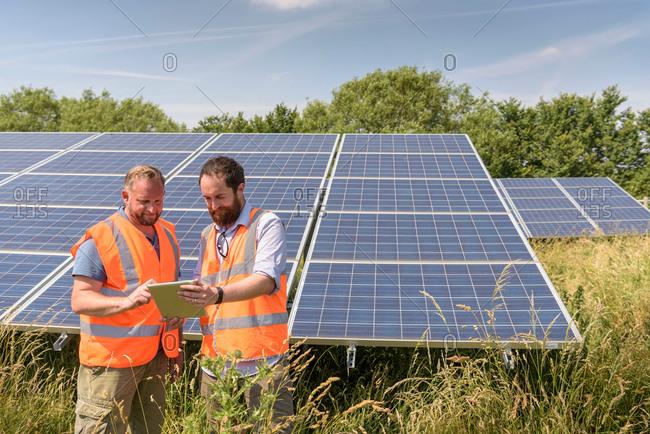 Local community members using digital tablet app to look at energy performance of solar farm