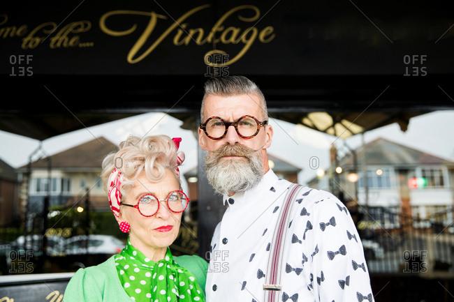 Serious portrait of a quirky vintage couple outside vintage shop