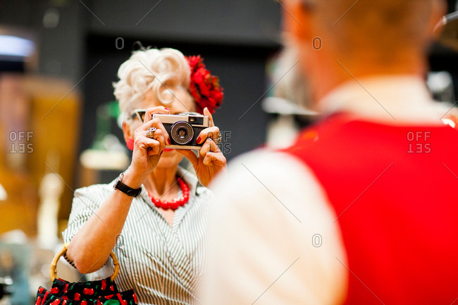 Quirky vintage woman photographing boyfriend on vintage camera in antiques emporium
