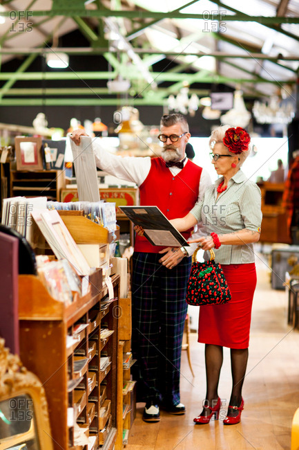 Quirky vintage couple looking at pictures in antique and vintage emporium