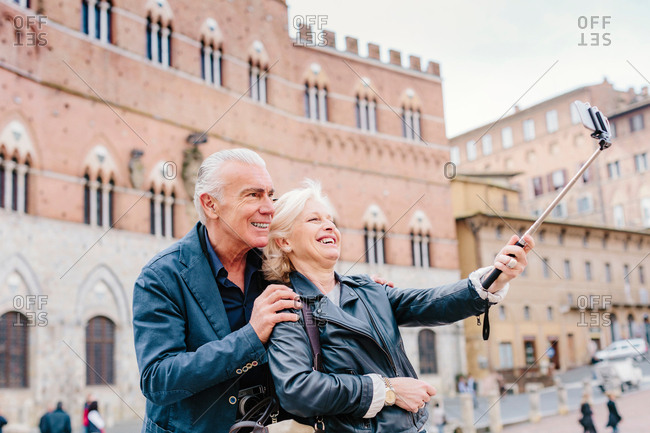 Tourist couple using selfie stick in city, Siena, Tuscany, Italy
