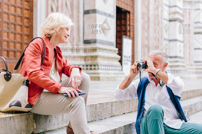 Senior male tourist photographing wife on Siena cathedral stairway, Tuscany, Italy
