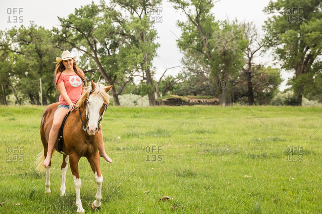 Young woman riding bareback on horse in ranch field, Bridger, Montana, USA