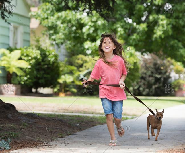 Girl walking dog in street