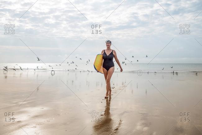 Woman carrying surfboard on beach, Folkestone, UK