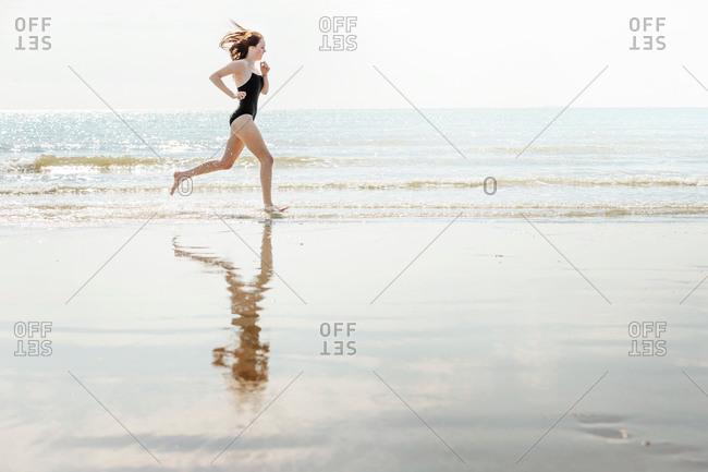 Young woman running on beach, Folkestone, UK