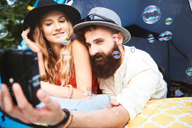 Young boho couple lying in tent taking selfie at festival