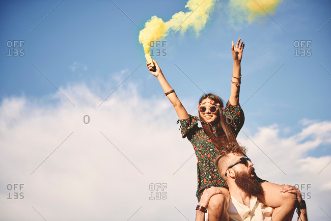 Young boho woman holding yellow smoke flare on boyfriend's shoulders at festival