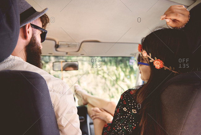 Over shoulder view of young boho couple with feet up in recreational van