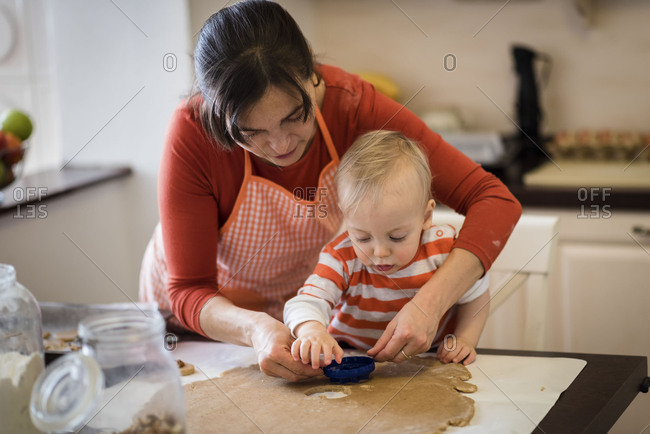 Mother helping kid cut different cookie shapes
