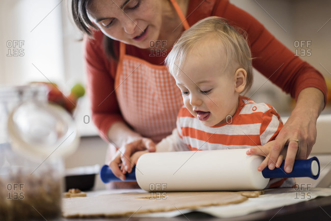 Mother helping child roll dough in kitchen