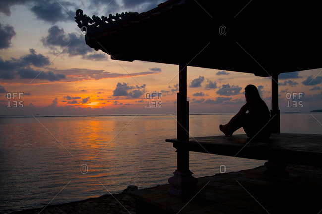 Silhouetted woman watching Balinese sunrise